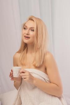 目をそらして、牛乳のカップと一緒にベッドに座っている若い女性