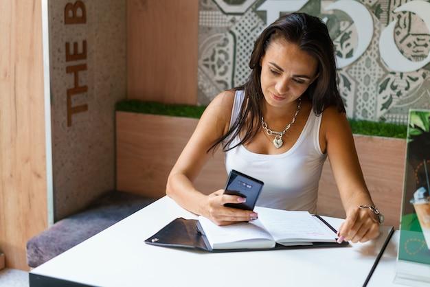 카페 테이블에 앉아 스마트폰으로 메시지를 입력하는 젊은 여성. 중년 블로거가 앱으로 메모를 하고 있습니다. 카페 내부에서 일하는 동안 스마트폰으로 책을 읽는 비즈니스 우먼.