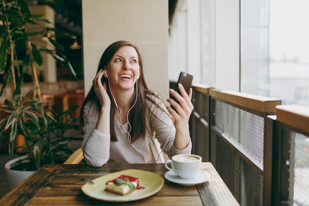 Молодая женщина, сидя в кафе за столом с чашкой капучино, тортом, расслабиться в ресторане в свободное время. молодые девушки слушают музыку в наушниках на мобильном телефоне, отдыхают в кафе. концепция образа жизни.