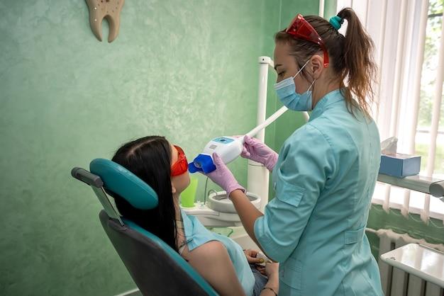 医師の管理下で美白手順を行う歯科医の椅子に座っている若い女性