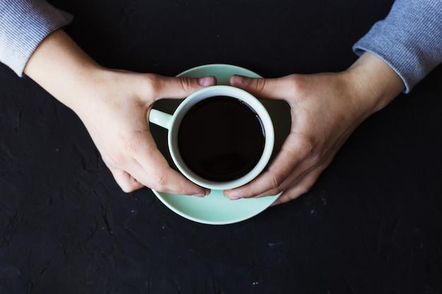 一杯のコーヒーと食堂に座っている若い女性