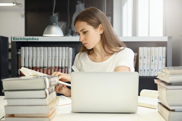 Молодая женщина, сидящая в библиотеке с ноутбуком