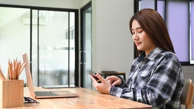 Молодая женщина, сидя в офисе и используя мобильный телефон.