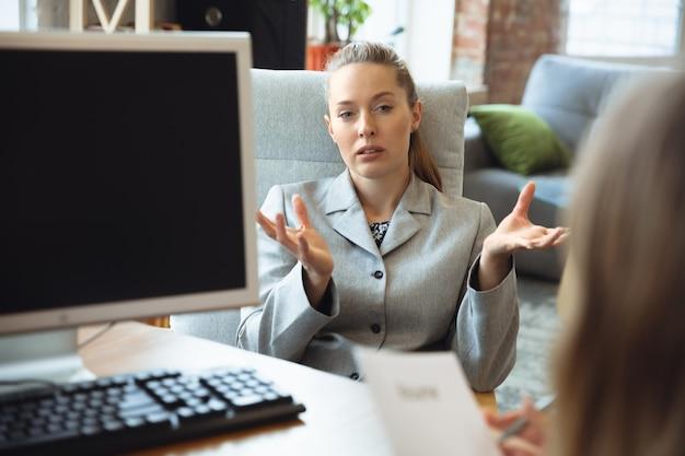 Молодая женщина сидит в офисе во время собеседования с сотрудницей, боссом или менеджером по персоналу, разговаривает, думает, выглядит уверенно. концепция работы, получение работы, бизнес, финансы, общение.