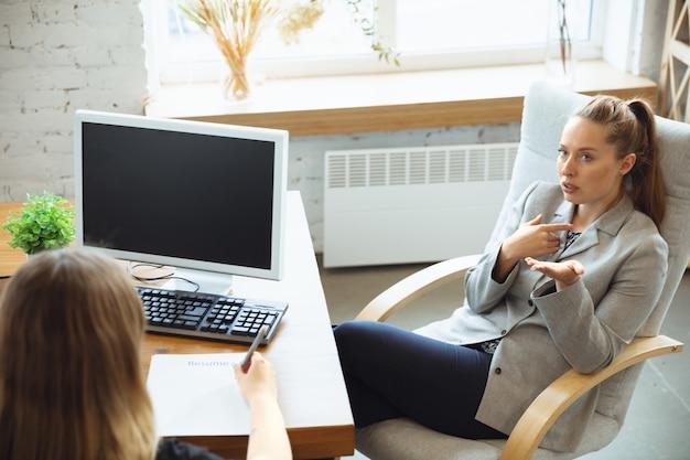 Молодая женщина сидит в офисе во время собеседования с работницей, начальником или hr-менеджером, разговаривает, думает, выглядит уверенно