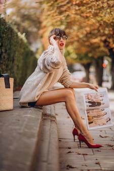 公園に座って読書をしている若い女性