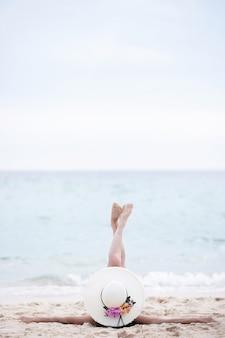 砂、体の部分と熱帯のビーチで屋外のリラクゼーションに座っている若い女性。日焼けした日光浴の女の子