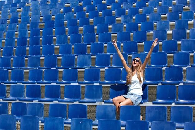 Молодая женщина, сидя на стадионе, приветствуя