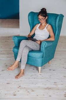 안락의자에 앉아 태블릿을 사용하는 젊은 여성