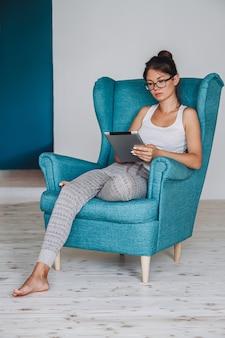 肘掛け椅子に座ってタブレットを使用して若い女性