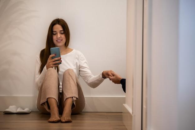若い女性が彼女の手で携帯電話で廊下に座って、彼女のパートナーと握手します。