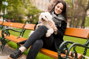 Young woman sitting in the park and holding a small dog in her lap