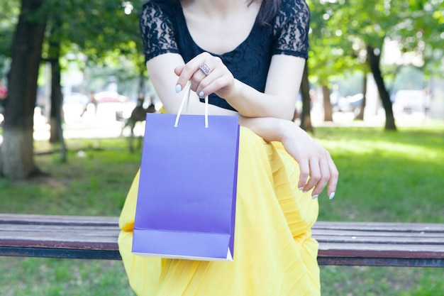 선물 가방 공원에 앉아 젊은 여자