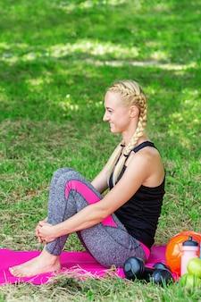 Молодая женщина, сидя в общественном парке.