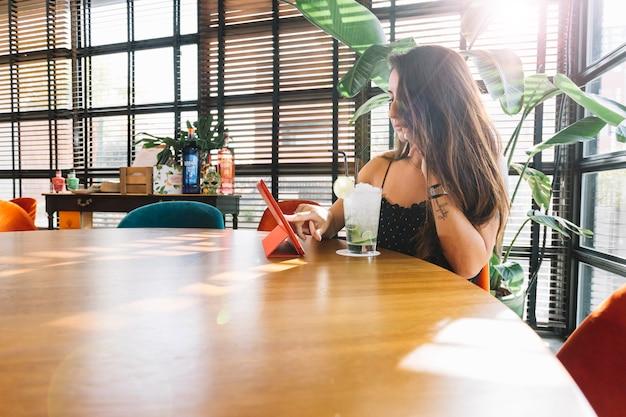 デジタルタブレットを使用してレストランに座っている若い女性