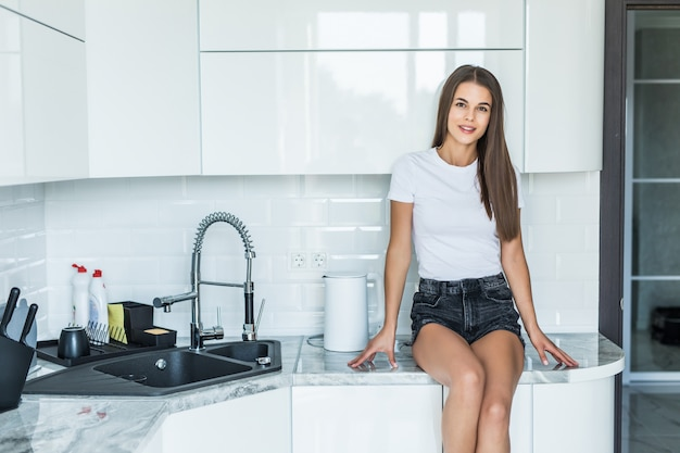 Young woman sitting on kitchen counter at home