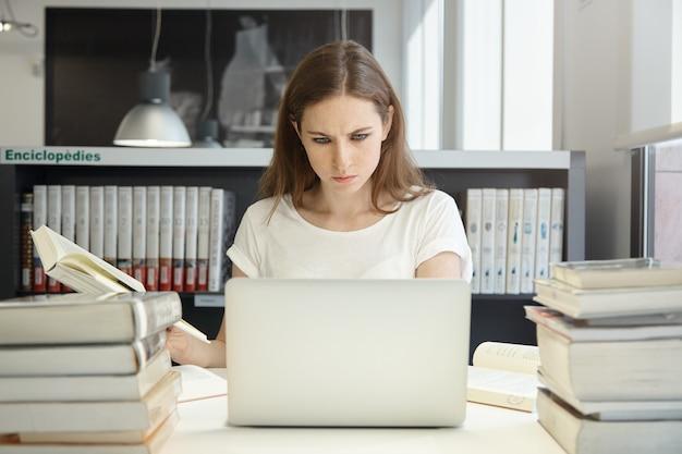 Giovane donna seduta in libreria con il computer portatile