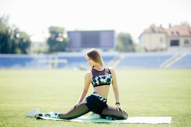 Young woman sitting on light green yoga mat stretching her back, legs, and body