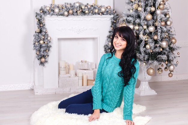 Young woman sitting in a living room with christmas decoration