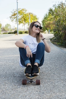 Young woman sitting on longboard and smiling