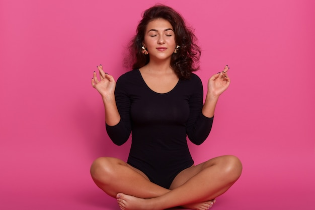 Young woman sitting in lotus position with closed eyes, doing yoga, relaxing at home, wearing black combidress, having wavy hair, sitting on floor on pink concentrated wall.
