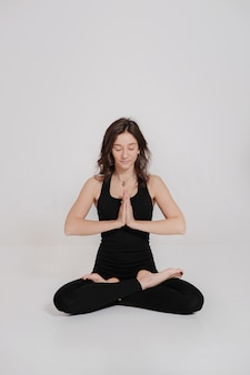 Young woman sitting in lotus posture in yoga class