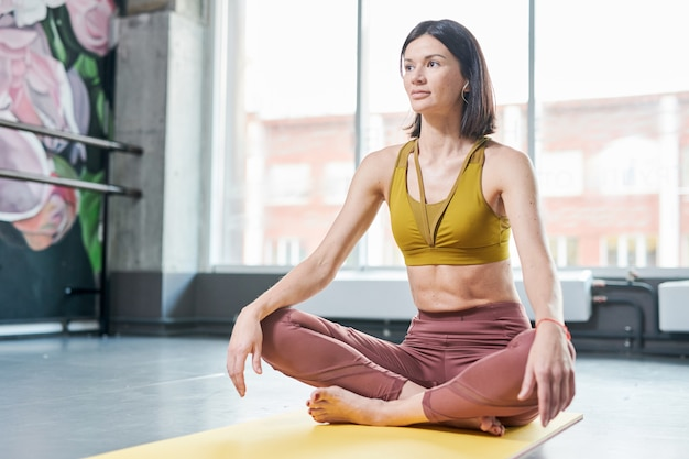 Young woman sitting on mat in gym