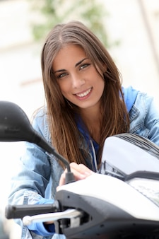 Young woman sitting on motorbike outside