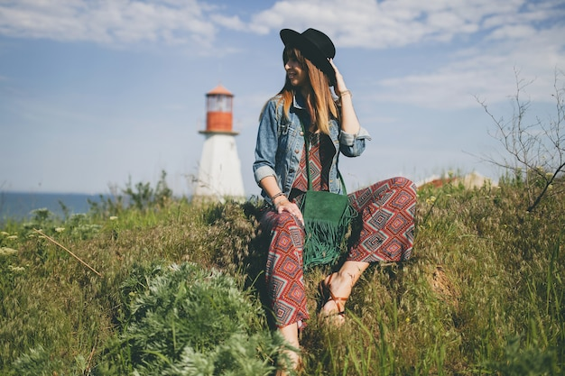 Young woman sitting in nature, lighthouse, bohemian outfit, denim jacket, black hat, smiling, happy, summer, stylish accessories