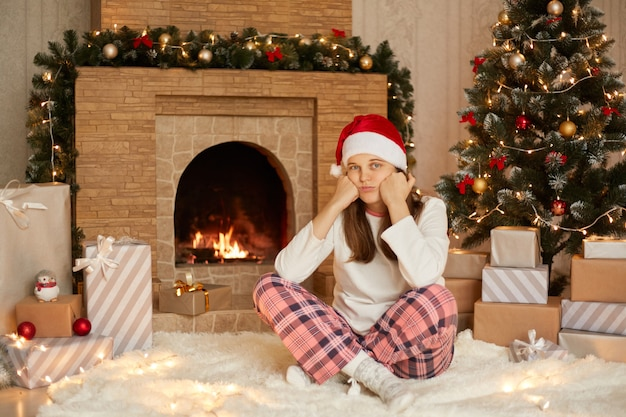 Young woman sitting over near fireplace, xmas tree and gift boxes with crossed legs, wearing christmas hat, white jumper and checkered pants, looking tired and bored with depression problems.