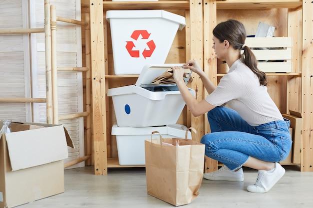 ゴミ箱の近くに座って、倉庫で他の廃棄物から紙を分離する若い女性