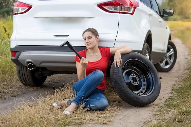 부서진 차 옆에 앉아 펑크난 타이어를 바꾸려고 하는 젊은 여성