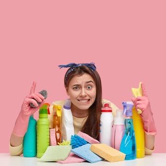 Молодая женщина, сидящая рядом с чистящими средствами