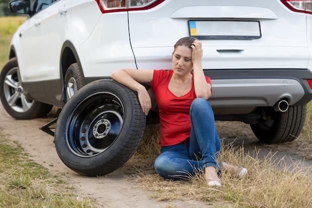 타이어 펑크가 난 차 옆에 앉아 있는 젊은 여성