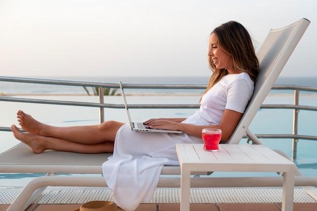 彼女の膝の上にラップトップを持ってプールの隣に座っている若い女性