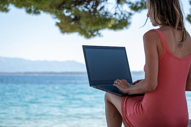 松の木陰のビーチに座って、ラップトップ コンピューターで作業する若い女性。