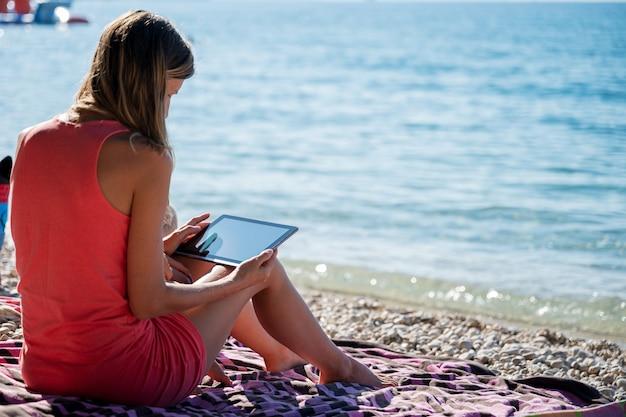 젊은 여자는 그녀의 디지털 태블릿에 아침 바다 브라우징으로 비치 타월에 앉아.