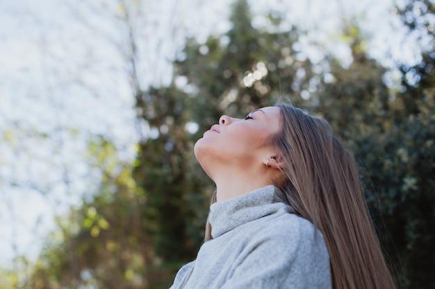 Молодая женщина, сидя на большой камень