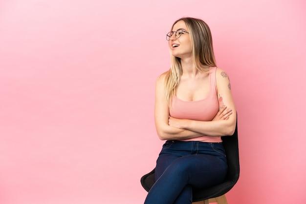 격리된 분홍색 배경 위에 의자에 앉아 행복하고 웃는 젊은 여성