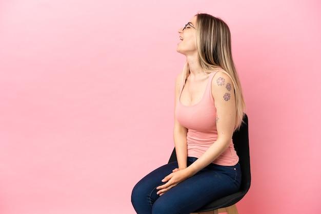 외진 분홍색 배경 위에 의자에 앉아 옆으로 웃고 있는 젊은 여성