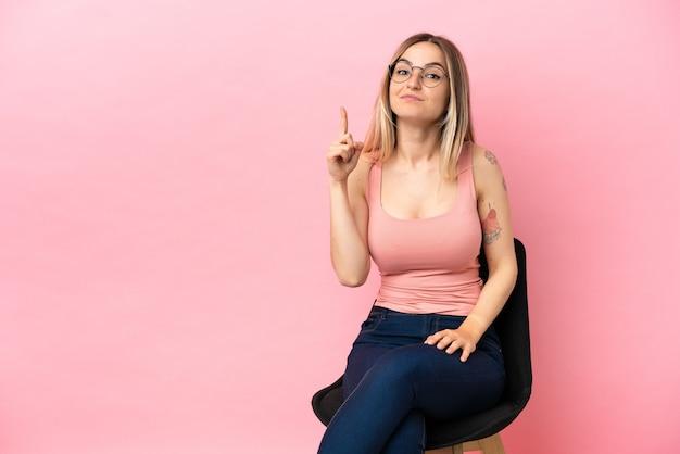 격리된 분홍색 배경 위에 의자에 앉아 검지 손가락으로 좋은 아이디어를 가리키는 젊은 여성