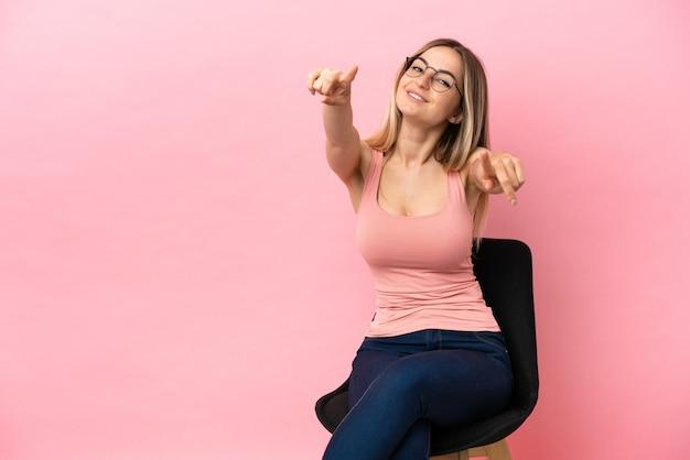 격리된 분홍색 배경 위에 의자에 앉아 있는 젊은 여성이 웃고 있는 동안 당신을 손가락으로 가리킵니다