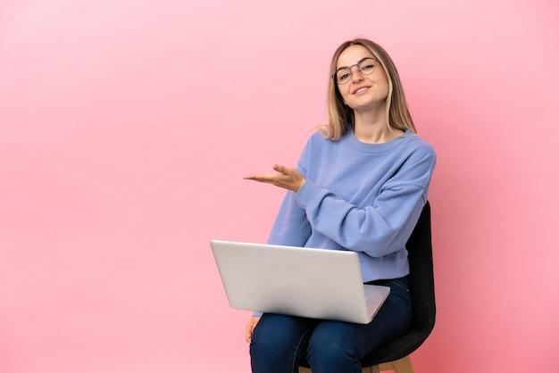 격리된 분홍색 배경 위에 노트북이 있는 의자에 앉아 있는 젊은 여성이 웃고 있는 동안 아이디어를 제시합니다.