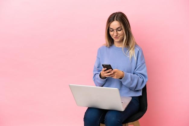 Молодая женщина сидит на стуле с ноутбуком на изолированном розовом фоне, отправляя сообщение с мобильного телефона