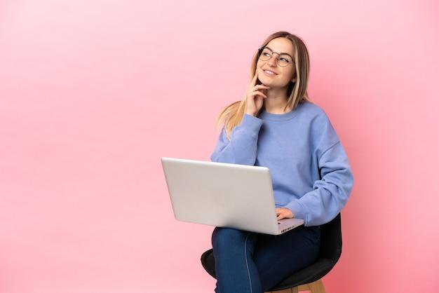 Молодая женщина, сидящая на стуле с ноутбуком на изолированном розовом фоне, думает об идее, глядя вверх