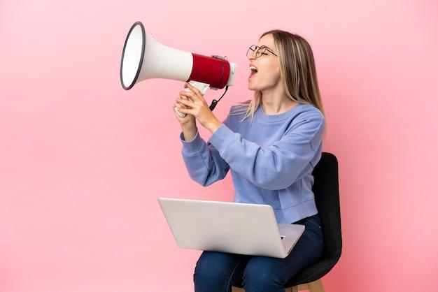 Молодая женщина, сидящая на стуле с ноутбуком над изолированной розовой стеной, кричит в мегафон