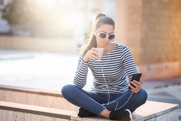 Молодая женщина сидит на городской улице и пьет кофе с собой и пользуется мобильным телефоном