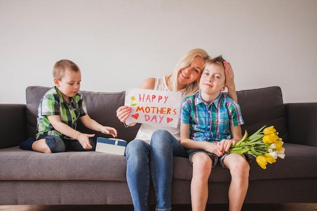 彼女の子供たちとソファに座っている若い女性