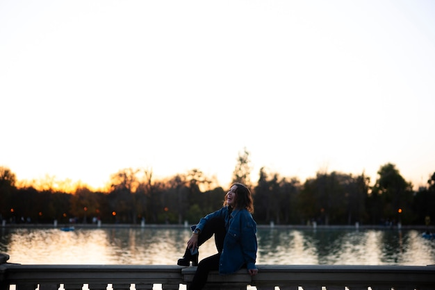 Молодая женщина, сидящая на заборе у озера