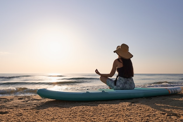 Молодая женщина, сидящая на доске с веслом в расслабляющей позе на восходе солнца на пляже